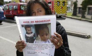 La mère du garçonnet disparu depuis vendredi dans la commune de Butry-sur-Oise (Val-d'Oise) tient un portrait de son enfant, le 25 avril 2015