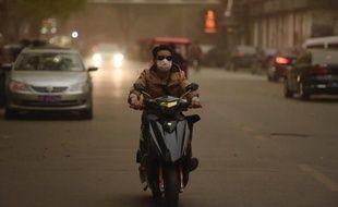 Un homme se protège de la pollution dans une rue de Pékin, le 15 avril 2015