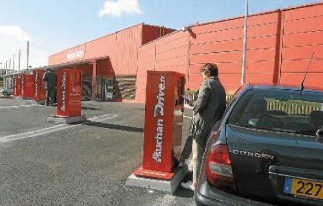 Un client se déplace en voiture pour retirer ses courses, commandées plus tôt sur Internet.