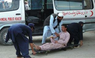 Des secours prennent en charge un blessé après l'attentat suicide dans un centre d'enregistrement électoral situé dans une mosquée, le 6 mai 2018 en Afghanistan.