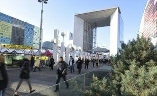 Des gens marchent près de la Grande arche de La Défense, quartier d'affaires de Paris, le 9 décembre 2015.