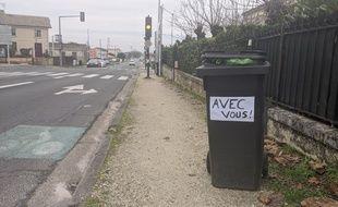 Ces habitants affichent leur soutien aux éboueurs.
