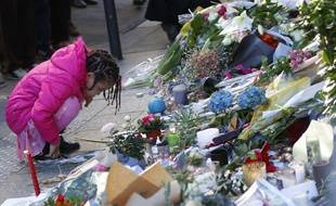 Proches et anonymes rendent hommage aux personnes décédées rue Bichat.