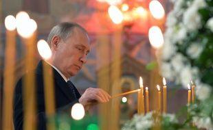 Le président russe, Vladimir Poutine, brûle un cierge dans une église de Pouchkine, près de Saint-Pétersbourg, le 8 décembre 2014.