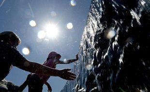 Une petite fille se rafraîchit dans une fontaine du parc Manezhnaya de Moscou, le 14 Mai2013.
