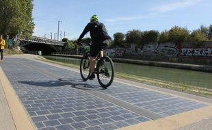 L'énergie produite par les dalles photovoltaïques permettent d'éclairer, en journée,  la portion de piste cyclable qui passe sous un pont, à quelques mètres de là.