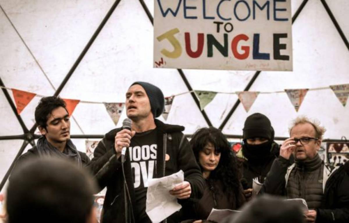"""Jude Law (au micro) dans un théâtre informel de la """"jungle"""" de Calais, le 21 février 2016 – PHILIPPE HUGUEN AFP"""