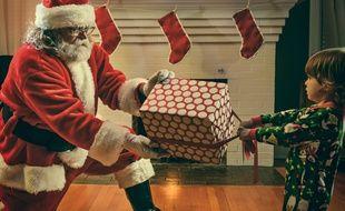 Un père Noël qui hésite à donner un cadeau à un enfant.