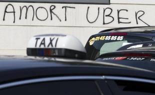 Un graffiti hostile à Uber, alors que des chauffeurs de taxi manifestent près de la Porte Maillot, à Paris, le 29 juin 2015