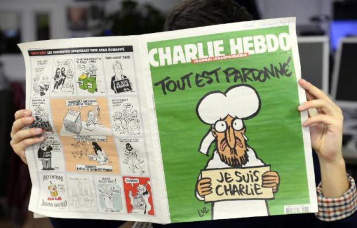 Un homme lit le dernier numéro de Charlie Hebdo à Paris le 13 janvier 2015 – Bertrand Guay AFP