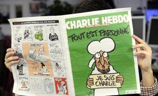 Un homme lit le dernier numéro de Charlie Hebdo à Paris le 13 janvier 2015
