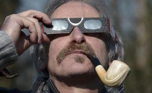 Un homme regarde l'éclipse solaire partielle à travers des lunettes de protection, le 20 mars 2015, à Strasbourg