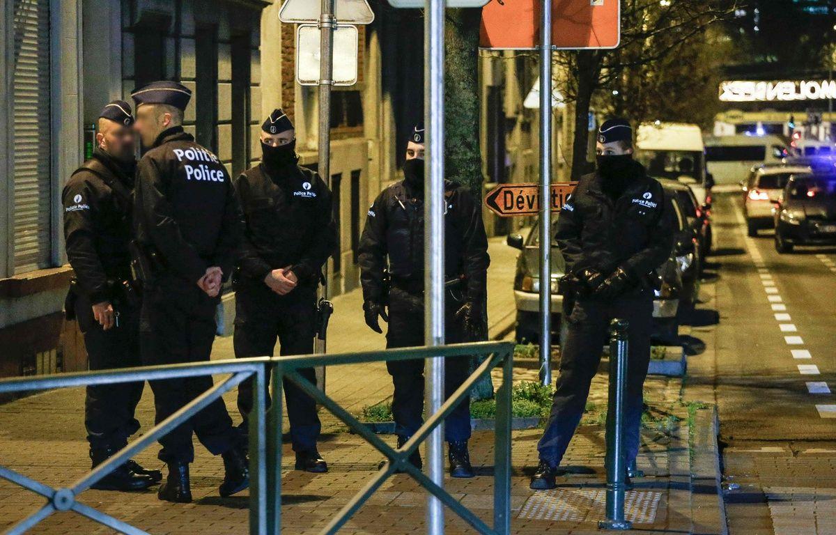 Des agents de police lors d'une perquisition dans le cadre de l'enquête sur les attentats de Paris, le 30 décembre 2015, à Molenbeek, près de Bruxelles, en Belgique. – AFP
