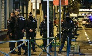 Des agents de police lors d'une perquisition dans le cadre de l'enquête sur les attentats de Paris, le 30 décembre 2015, à Molenbeek, près de Bruxelles, en Belgique.