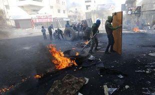 Des Palestiniens se protègent derrière une porte lors d'affrontements avec l'armée israélienne à Hébron le 3 avril 2013.