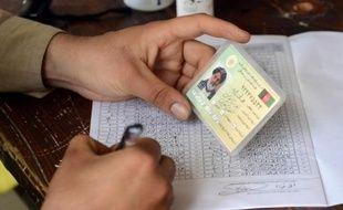Vérification de l'identité d'un électeur, dans un bureau de vote de Kaboul le 5 avril 2014