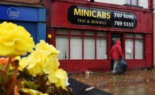 Des fleurs déposées devant l'agence de taxis où avait travaillé l'humanitaire britannique assassiné, Alan Henning, à Eccles au nord-ouest de l'Angleterre, le 4 octobre 2014
