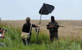 Un séparatiste pro-russe cagoulé sur le site du crasjh de l'avion malaisien à Grabove, le 19 juillet 2014
