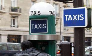 Un homme appelle un taxi à une borne prévue à cet effet, en octobre 2002 à Paris.