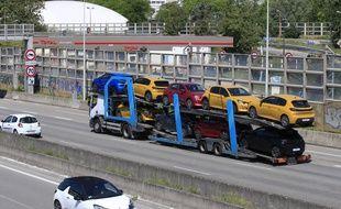 Un camion transporte de nouvelles voitures sur l'autoroute menant à Paris, le mardi 26 mai 2020 à Villacoublay, à l'ouest de Paris.
