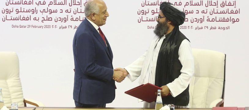 Zalmay Khalilzad et Mullah Abdul Ghani Baradar se serrent la main après la signature de l'accord, à Doha, au Qatar, le 29 février 2020.