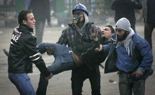 Des manifestants égyptiens évacuent l'un des leurs, blessés dans les heurts qui les opposent aux forces de l'ordre, le 17 décembre 2011, au Caire.