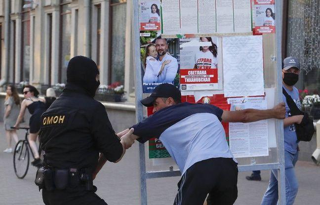 Arrestation d'un opposant au président de Biélorussie devant des affiches électorales, à Minsk le 8 août 2020.