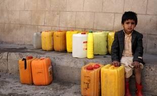 Un enfant attend la distribution d'eau potable au Yémen.