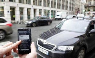 Utilisation de l'application Uber sur smartphone pour réserver une voiture, le 10 décembre 2014 à Paris