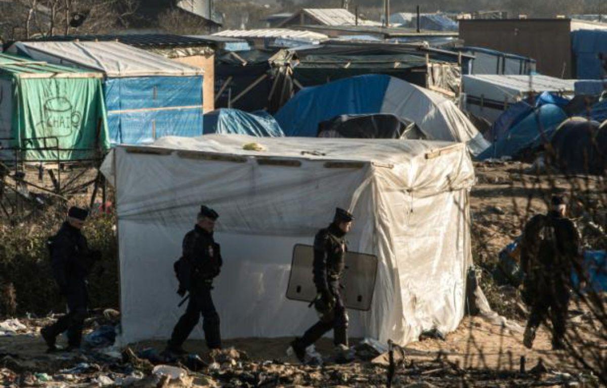 """Des policiers patrouillent dans le camp de migrants appelé la """"Jungle"""" à Calais, le 20 janvier 2016 – PHILIPPE HUGUEN AFP"""