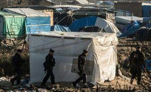 """Des policiers patrouillent dans le camp de migrants appelé la """"Jungle"""" à Calais, le 20 janvier 2016"""