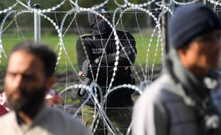 Un garde-frontière polonais surveille un camp de réfugiés derrière des barbelés installés à la frontière entre la Biélorussie et la Pologne près du village d'Usnarz Dolny, en Biélorussie.