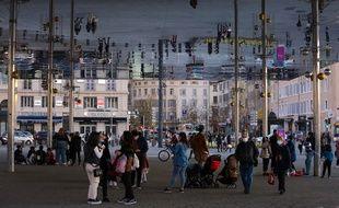 Des gens masqués en raison de l'épidémie de Covid-19 marchent sous l'ombrière du Vieux-Port de Marseille