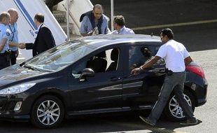 Le juge d'instruction de Mayotte Hakim Karki (3e d) arrive sous escorte policière le 7 juillet 2014 à l'aéroport Sainte-Marie de La Réunion
