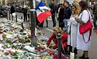 Des passants allument des bougies en hommage aux victimes des attentats du 13-Novembre, aux angles des rues Alibert et Bichat ainsi que devant la salle de spectacle du Bataclan.
