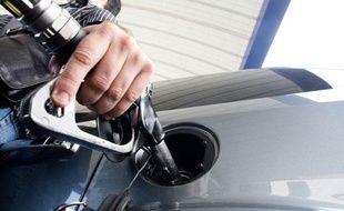 Un homme fait le plein de son réservoir d'essence, avec un pistolet à essence. Illustration station service.