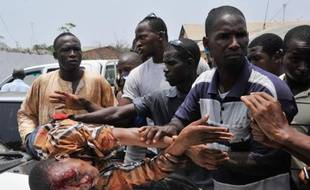 Des hommes assistent partisan de l'opposition guinéenne blessé dans des heurts avec les forces de l'ordre à Conakry le 20 avril 2015