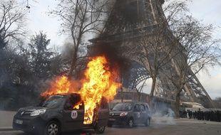 """Une voiture de Sentinelle brûle devant la Tour Eiffel, en marge d'une manifestation de """"Gilets jaunes"""" à Paris le 9 février 2019."""