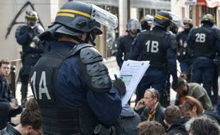 Des policiers vérifient l'identité de manifestants, le 1er, à Paris.