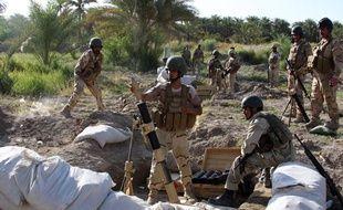 Des soldats irakiens, à 45 km de Bagdad, visent vers des positions djihadistes, le 6 août 2014, tandis que les djihadistes ont pris la plus grande ville chrétienne.