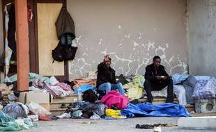 Migrants sit on the stairs of a building in Calais, northern France, on August 5, 2014. Dozens were hurt on August 5 after clashes broke out in the northern French port of Calais between hundreds of African migrants seeking to cross the Channel to England. Police reinforcements were called to break up fights between groups of mainly Eritrean and Sudanese migrants that left 51 people hurt, one of whom was sent by helicopter to hospital with serious head injuries.  AFP PHOTO / PHILIPPE HUGUEN