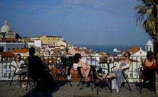 Des touristes profitent du soleil sur une terrasse, dans le quartier d'Alfama, le 15 avril 2014 à Lisbonne