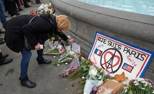 Une femme dépose  une gerbe de fleurs en hommage aux victimes de l'attentat à Trafalgar Square.