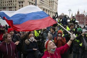 Un homme brandit le drapeau russe lors de la manifestation en soutien à Alexeï Navalny, à Moscou le 21 avril 2021.