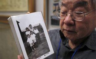 Un descendant d'une famille de Nippo-Américain pose avec une photo de sa famille internée pendant la guerre.