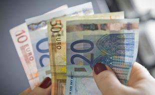 Paris le 04 fevrier 2013. Illustration epargne argent billet de banque tenus dans une main.
