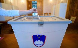 Un électeur dépose son bulletin dans l'urne le 20 décembre 2015 à Bled en Slovénie