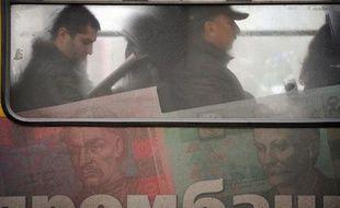 La valeur de la Hryvnia, la monnaie ukrainienne peinte ici sur les flancs d'un bus à Kiev, a été divisée par trois en un peu plus d'un an
