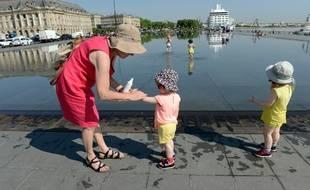 Une femme étale de la crème solaire sur le bras d'un enfant à Bordeaux.