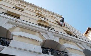 Un ouvrier répare des balcons sur la façade d'un immeuble de Marseille.
